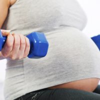 Young pregnant woman exercise with weights. Unrecognizable person.   [url=http://www.istockphoto.com/search/lightbox/9786766][img]http://dl.dropbox.com/u/40117171/sport.jpg[/img][/url]